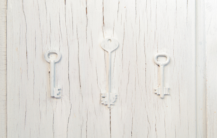 Three keys trendy decor on an old gray cracked door, vintage abstract design cluse-up background. Choice of path concern