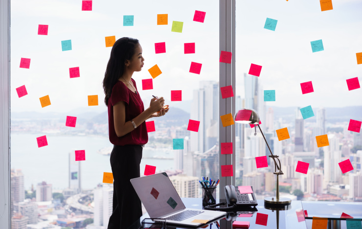 young woman standing in office writing on post it notes