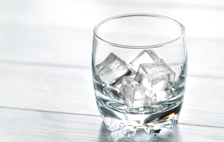 Glass with ice cubes on the wooden table