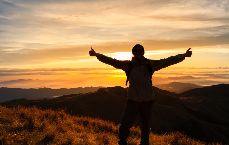 man on top of mountain at sunset