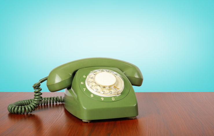 Vintage Phones - Green a retro telephone on a wooden table and a blue background.