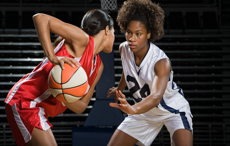 two women playing basketball