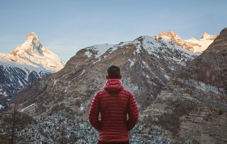 man in red jacket facing a mountain