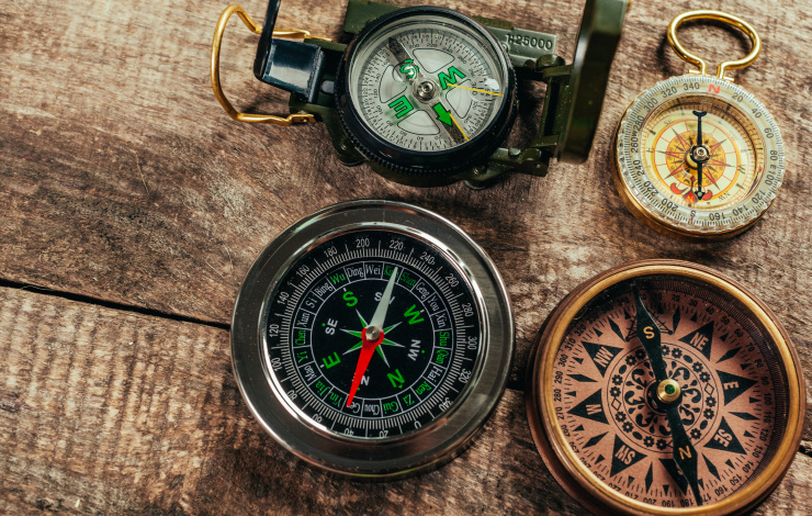Various compasses on a wooden deck