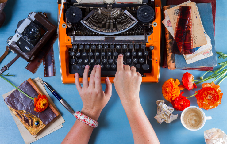 Workspace with someone hands typing on orange vintage typewriter on blue background