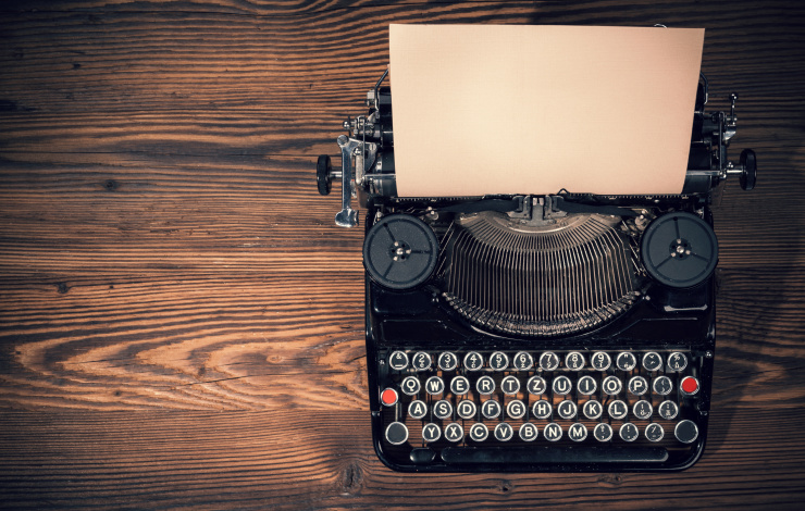 black typewriter on wood desk