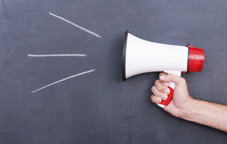 holding a megaphone against a chalkboard