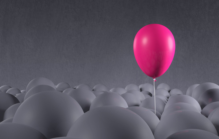 pink balloon floating above gray balloons