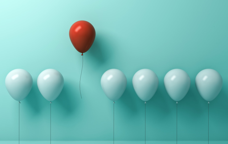 single red balloon standing out among white balloons