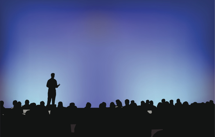 Person speaking in front of a crowd at a conference
