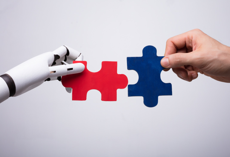 Robot and human hands holding puzzle pieces
