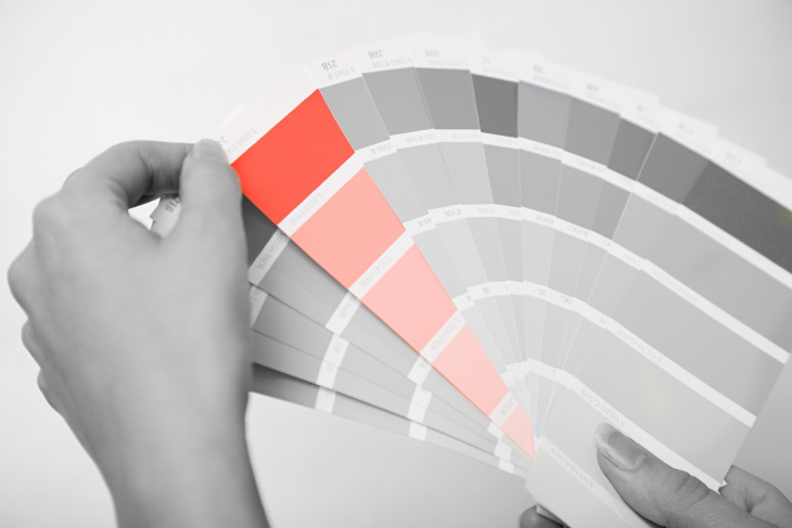 person selecting a paint color from a stack of paint chips