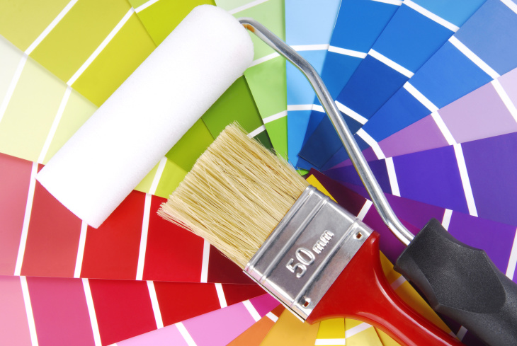 a paint brush and roller sitting on a large selection of paint chips