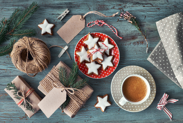 Wooden rustic background with cup of hot coffee and gift wrapping of Christmas cookies. Seasonal background shot from above. Flat lay, top view, filtered image. Tag mockup, copy space on the tags.