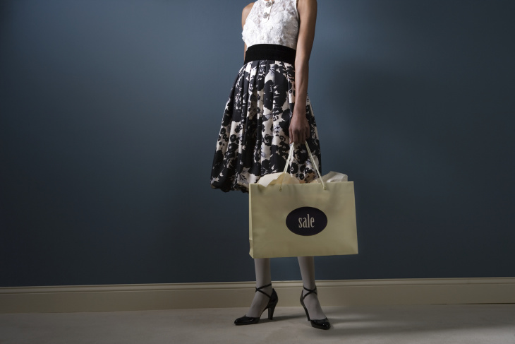 nicely dressed woman holding a shopping bag