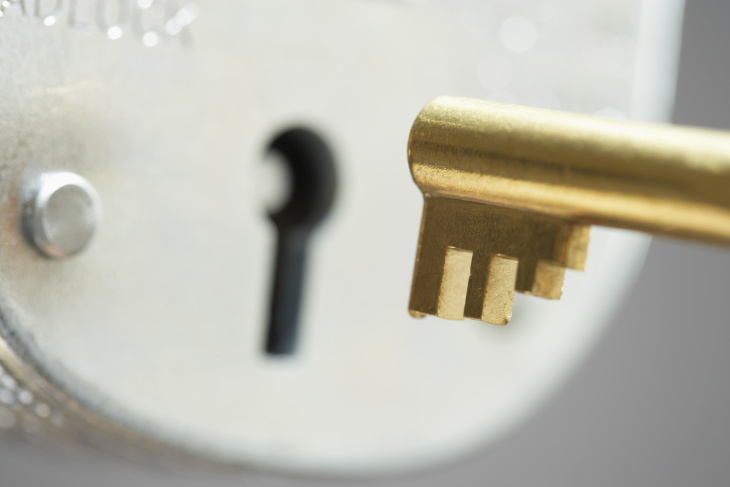 gold key going into lock
