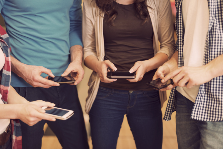 group of young people checking mobile phones