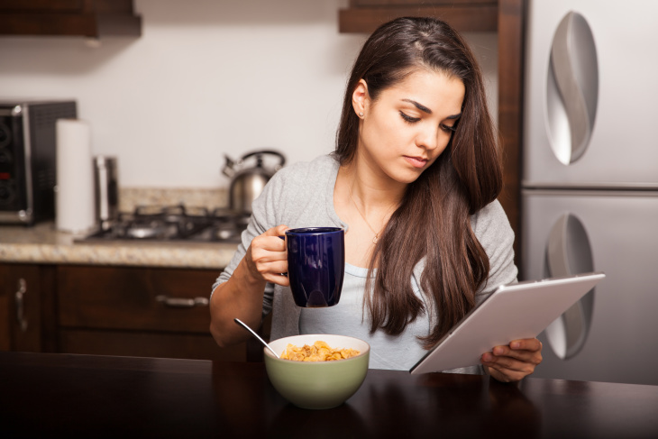 Young woman using a tablet computer to read the news and some emails while having breakfast at home