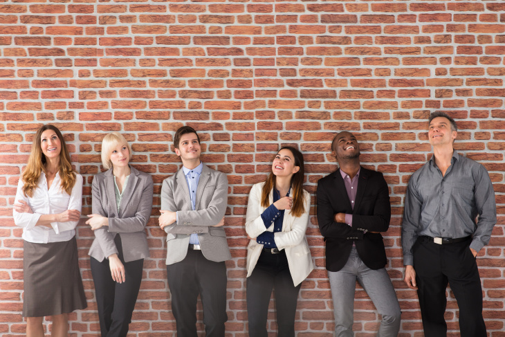Diverse Group Of Businesspeople Standing Near The Brick Wall Looking Up