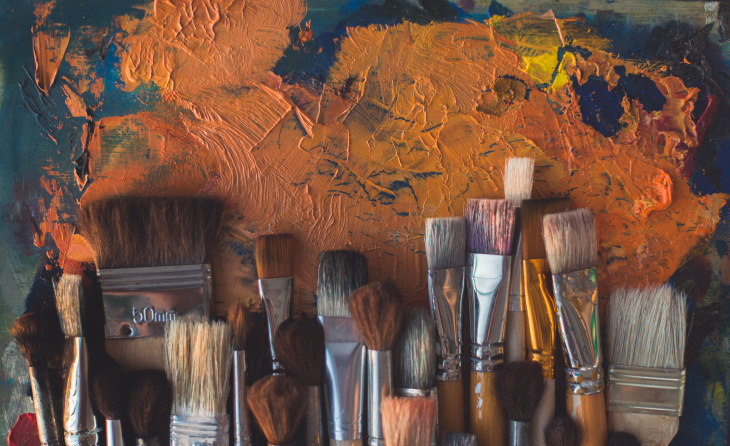 paint brushes and orange paint