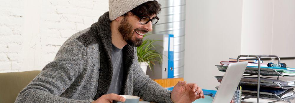 Happy bearded man on a laptop