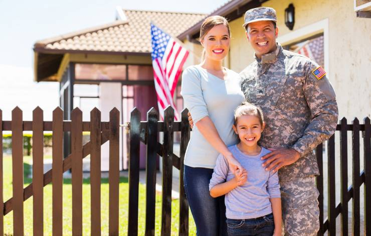 military family standing in front of house