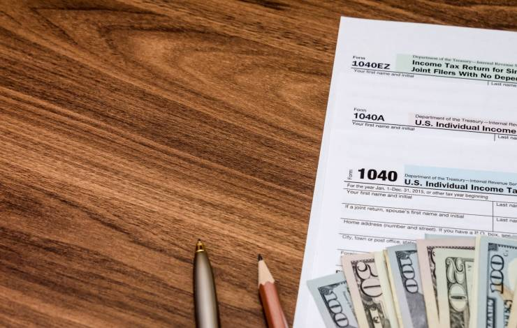 tax form on desk with cash and pens