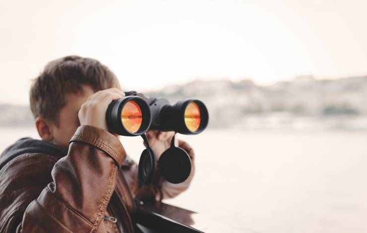 Little caucasian boy watching, looking, gazing, searching for by binoculars during trip