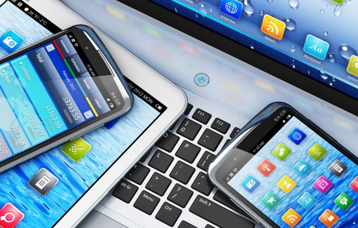 mobile phones with apps sitting on a computer and tablet