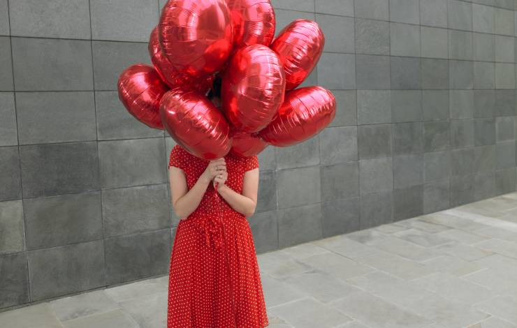 woman holding a bunch of red balloons in front of her face, concealing her identity.