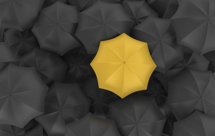 single yellow umbrella among black umbrellas