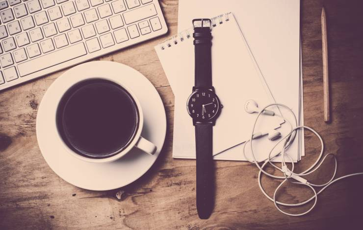 coffee, watch, earbuds, notepad and keyboard sitting on desk