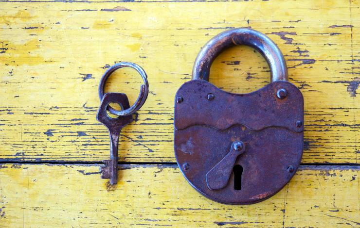 Old lock with a key on the background of wooden boards painted with yellow paint 3