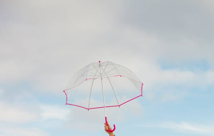 Weather, rain protection concept. Woman hand holding transparent umbrella, sunny day and clear blue sky
