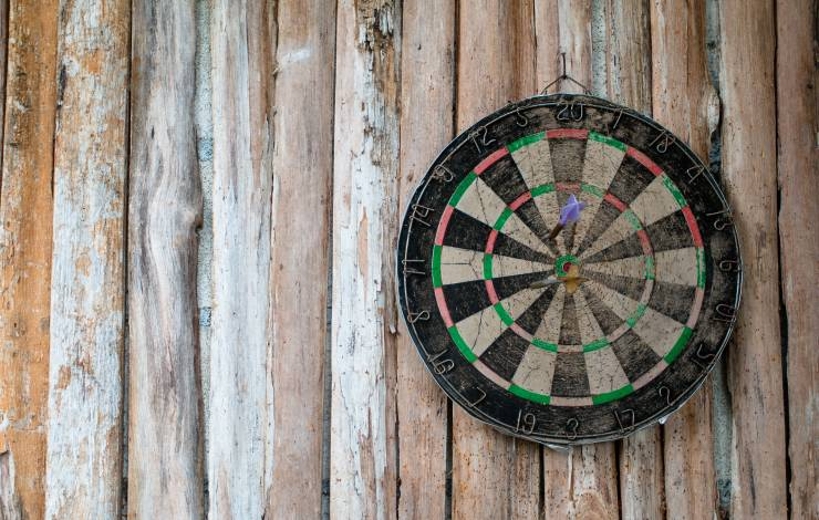 Old dart board on wooden background in concept long time to target or success