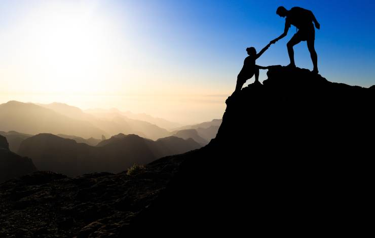 two people climbing a mountain, one person helping the other up to the summit