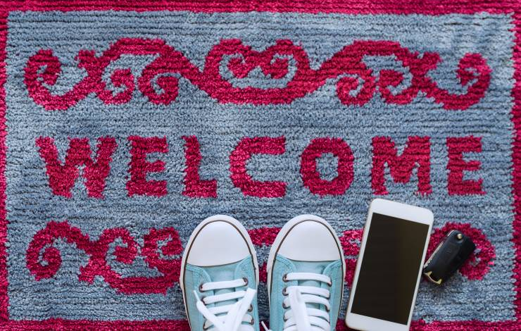 Welcome home carpet with shoes,smartphone and key of car on it,welcome concept.