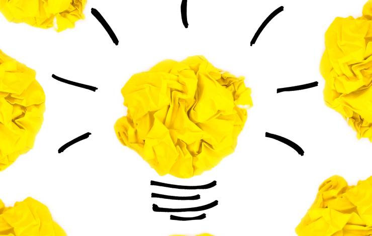 Creative concept. Yellow light bulb made of yellow crumpled, paper ball.
