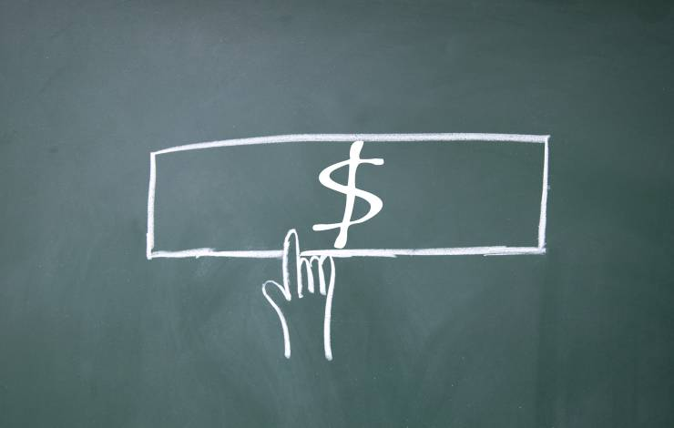 drawing of dollar on chalkboard with hand