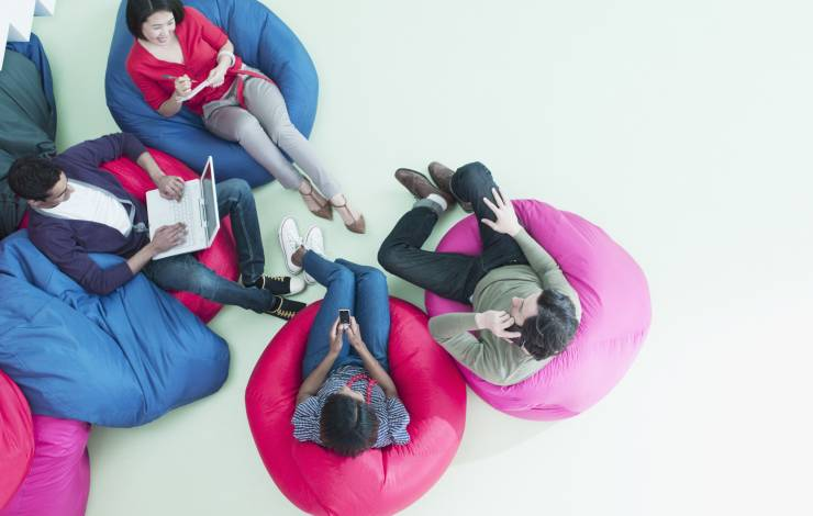 people sitting on beanbag chairs checking email