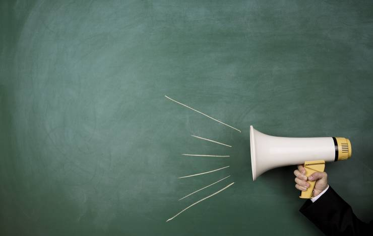 megaphone against a green chalkboard