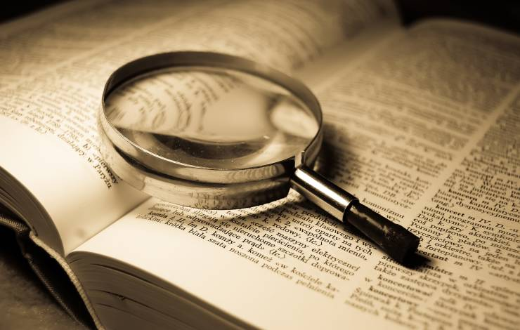 magnifying glass sitting on large case study book