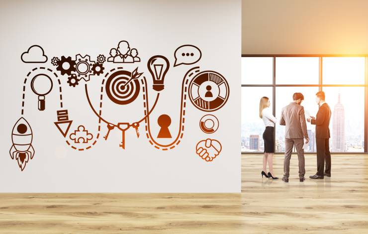 people standing in an empty office with an illustration of a start up