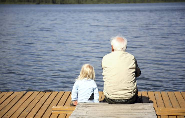 grandfather with girl sitting together on a lakeside dock
