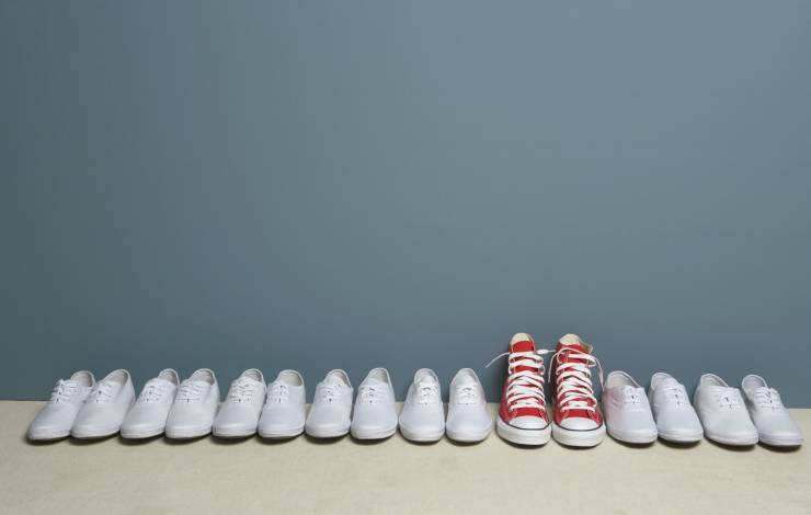a row of white shoes, with one exceptional pair of red converses.