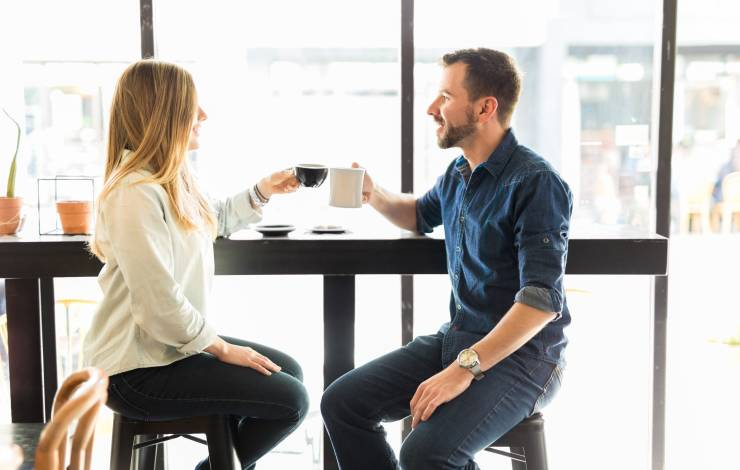 Coffee lovers having a good time together and making a toast with a cup of coffee at a cafe