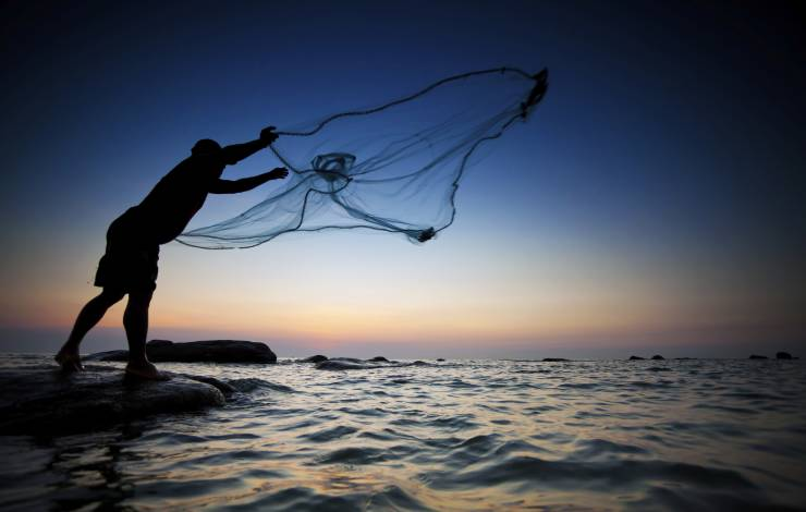 man casting net into ocean