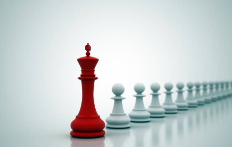 one red chess piece in front of small white chess pieces