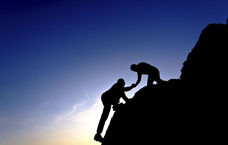 two business people scaling a mountain side. one is helping the other up.