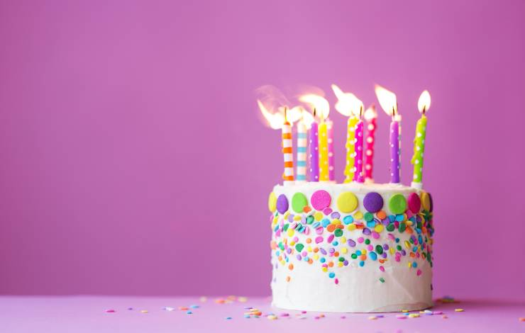 birthday cake with candles on a pink background